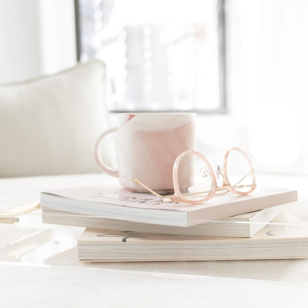 stack of books with coffee cup and glasses on top