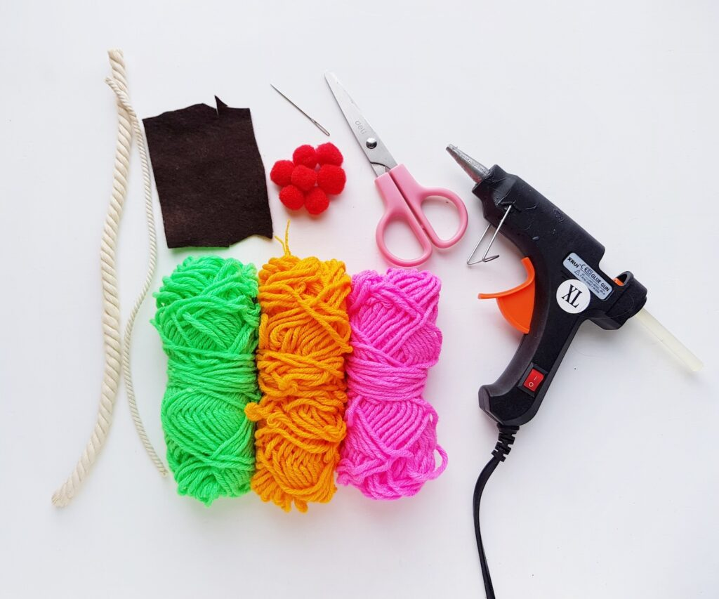 three skeins of yarn with hot glue gun and scissors on white background
