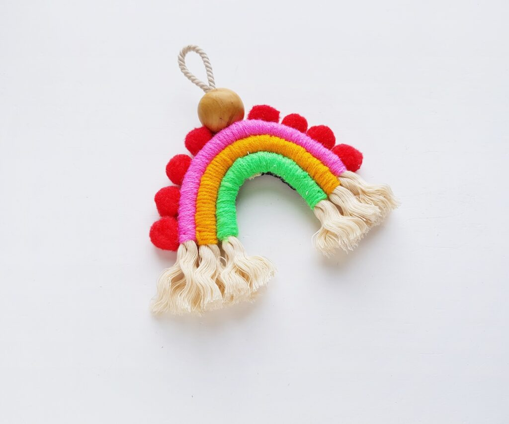 red pom poms on macrame rainbow wall hanging