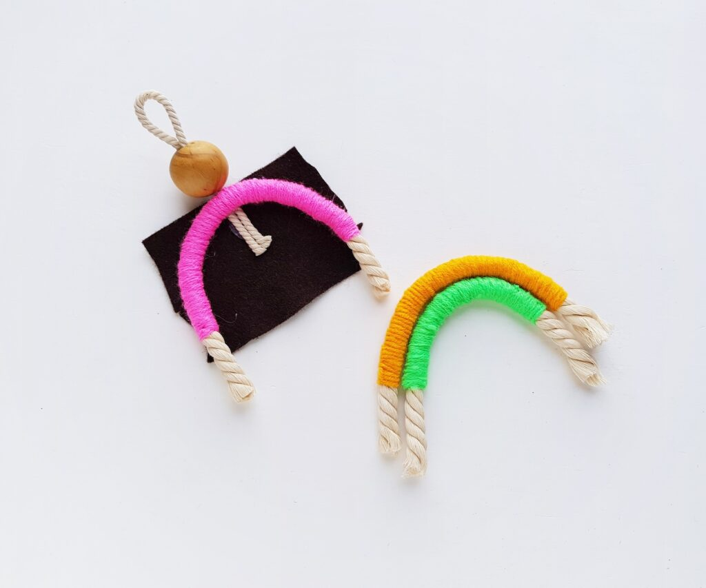 pieces of rope wrapped with brightly colored yarn glued to square of black felt