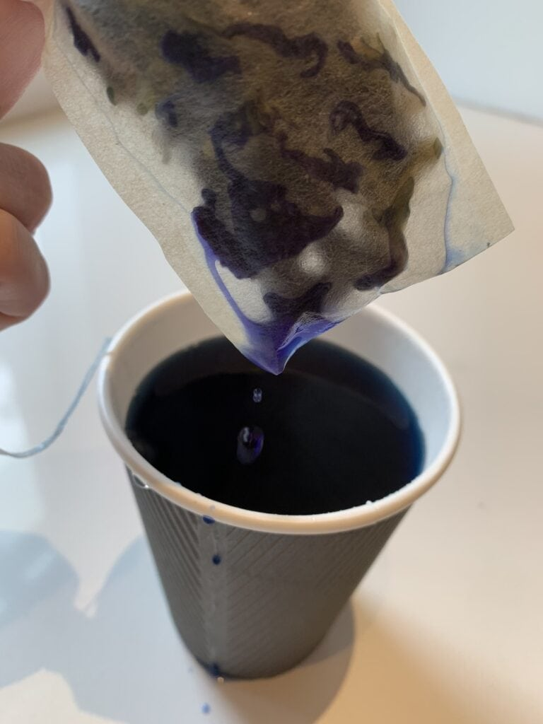 tea bag with blue tea dripping into a cup