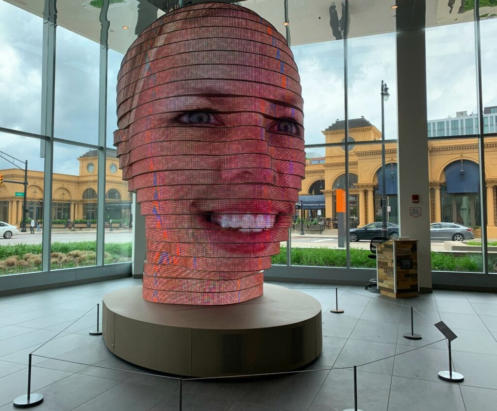 art statue head with digital display of a face on it