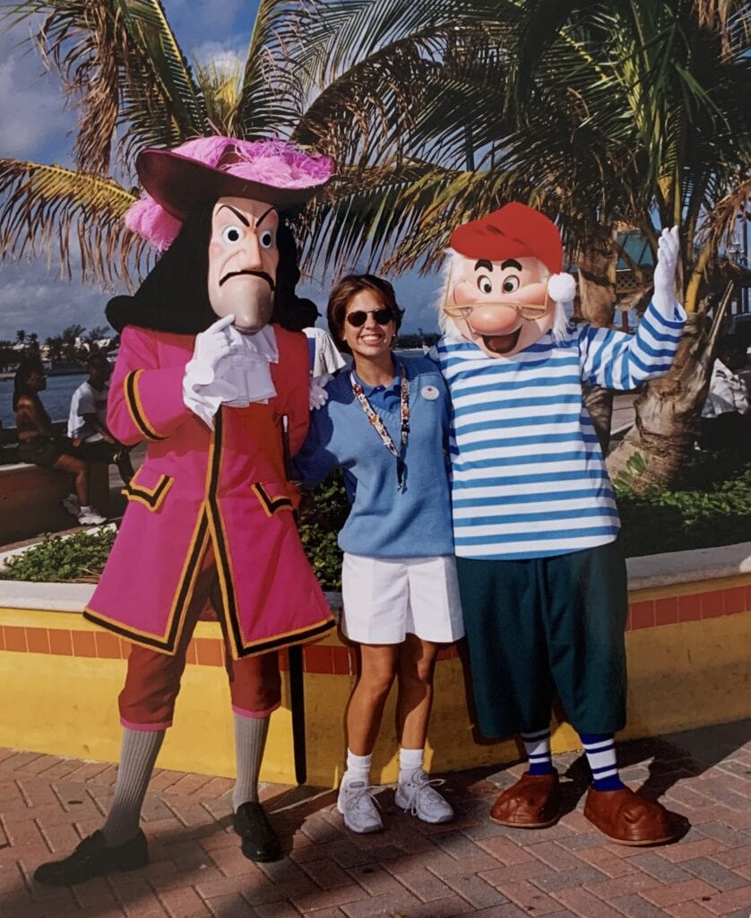 woman standing with Captain Hook and mr. smee characters in front of palm trees