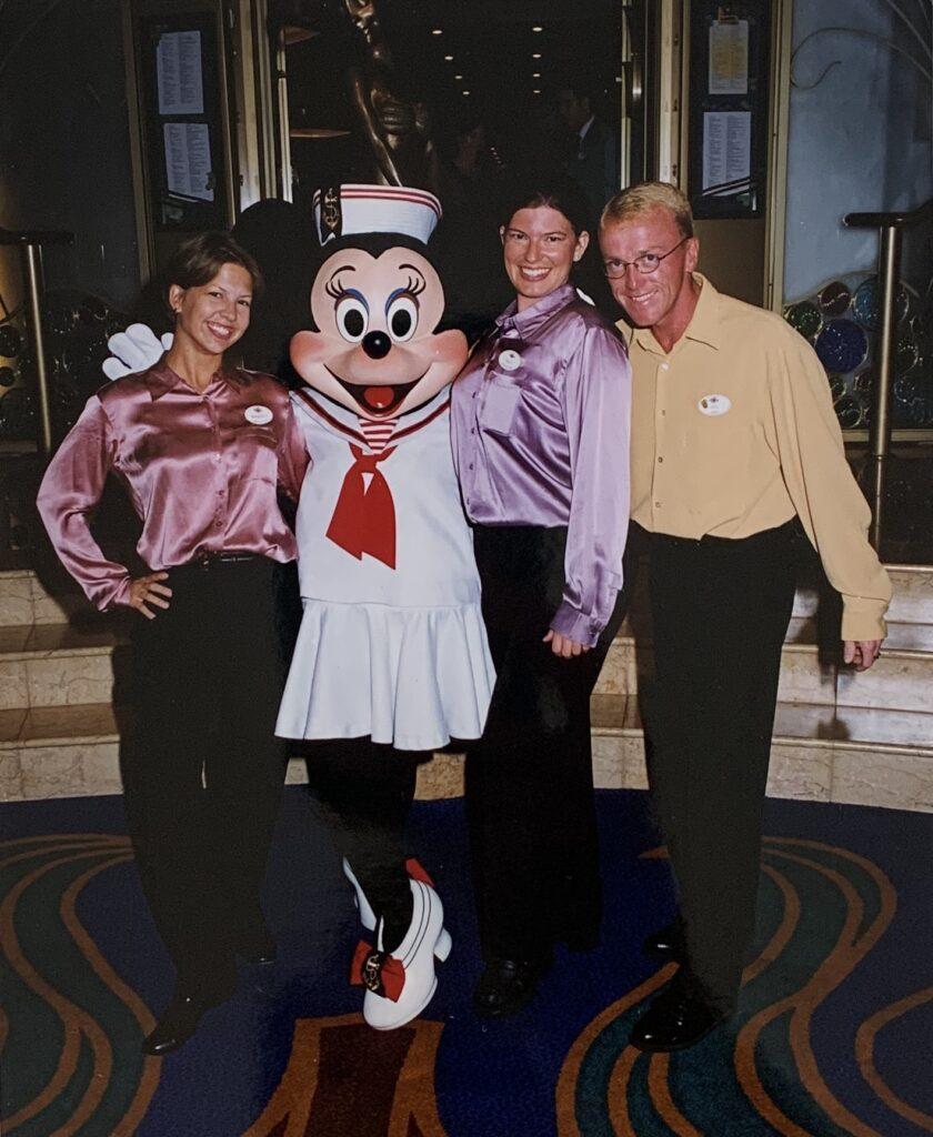 two girls and a guy posing with Minnie Mouse character