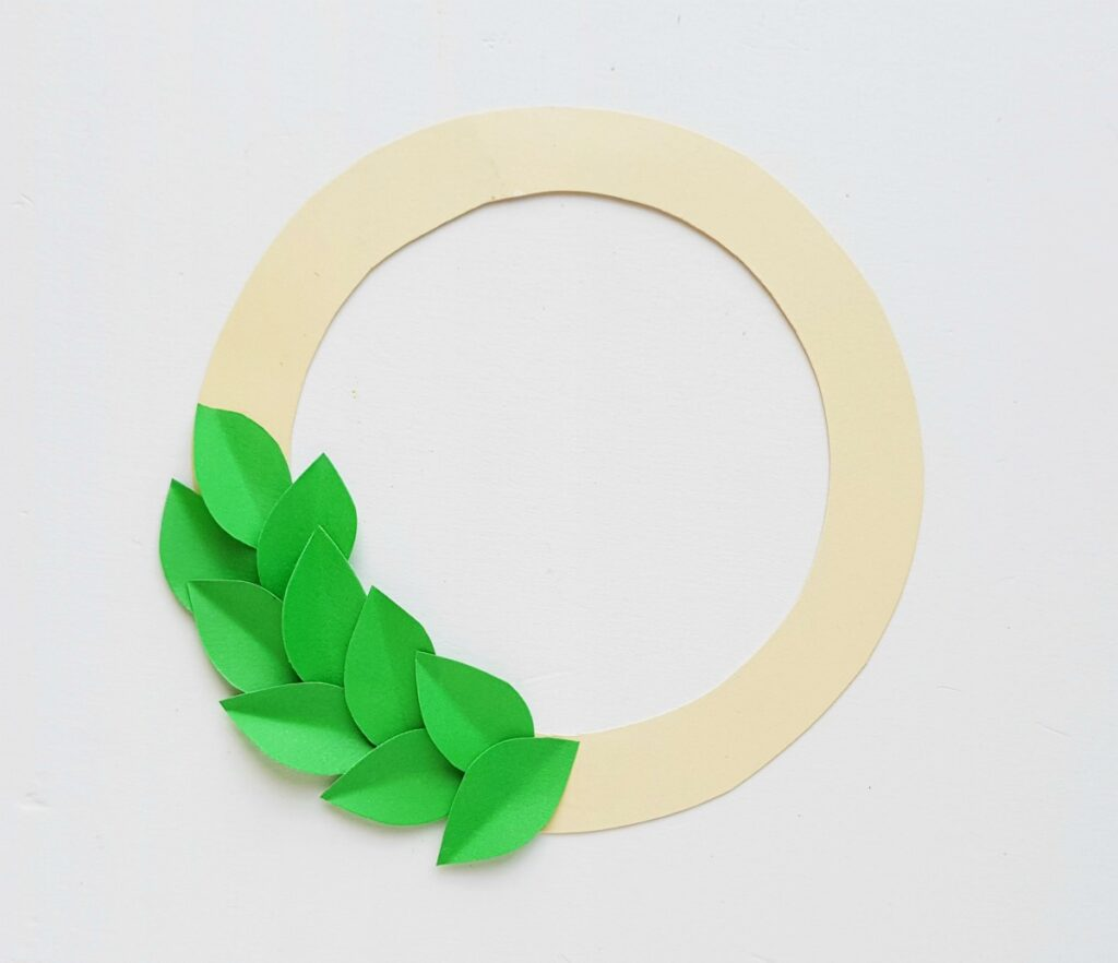 green paper leaves glued on a white paper wreath