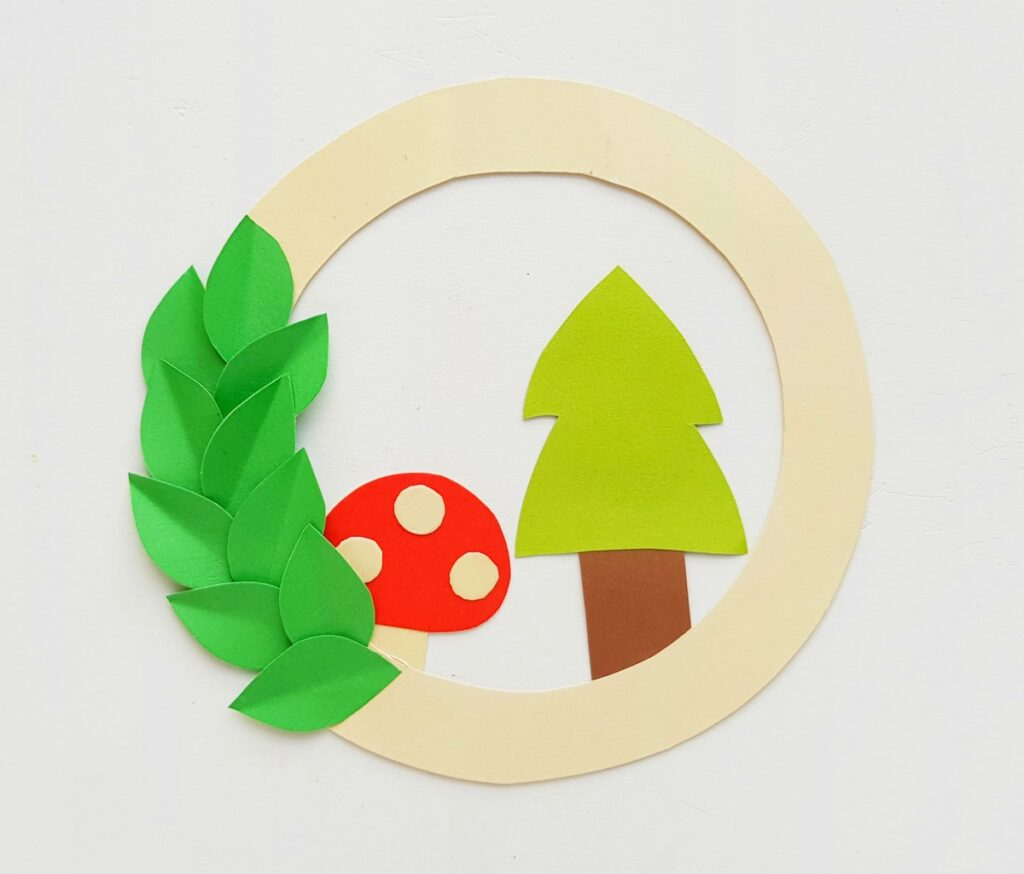paper mushroom and tree glued on paper wreath base