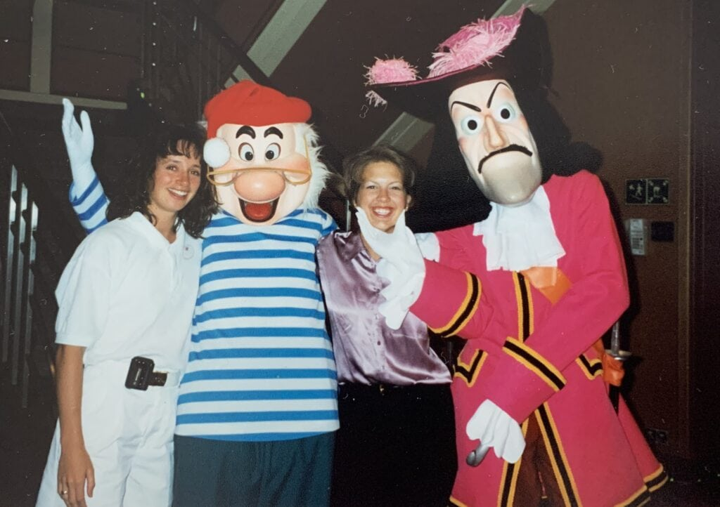 two women taking a picture with Captain Hook and mr. see onboard disney cruise line