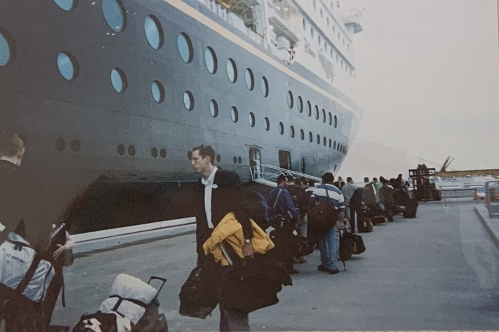 cruise line workers holding luggage getting on ship