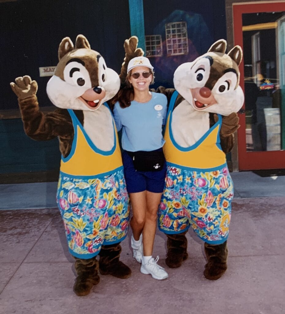 cruise ship worker posing with Chip and Dale wearing swimsuits