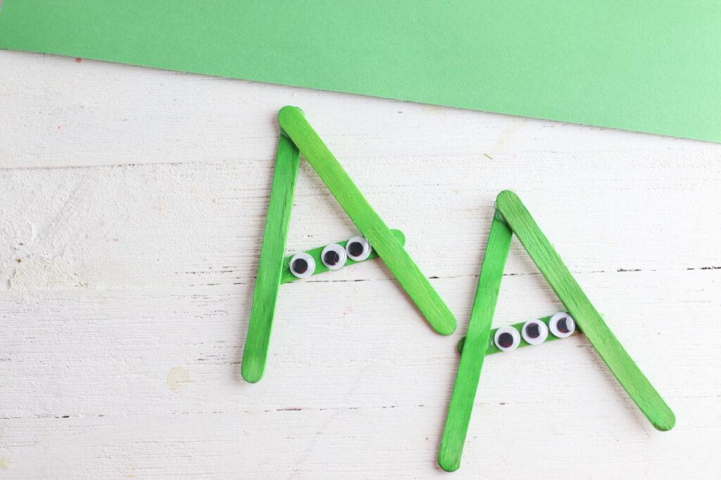 green popsicle sticks in shape of alien