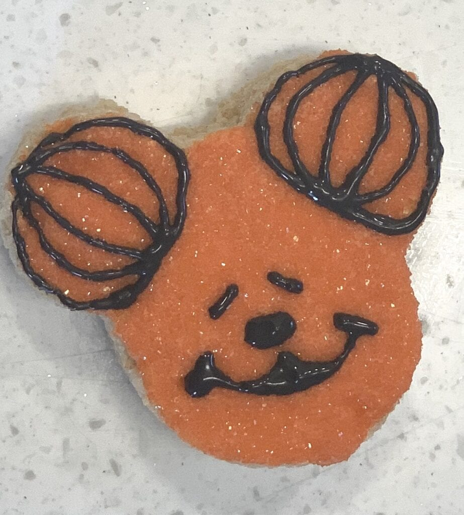 making Mickey Mouse face with frosting on snack treat