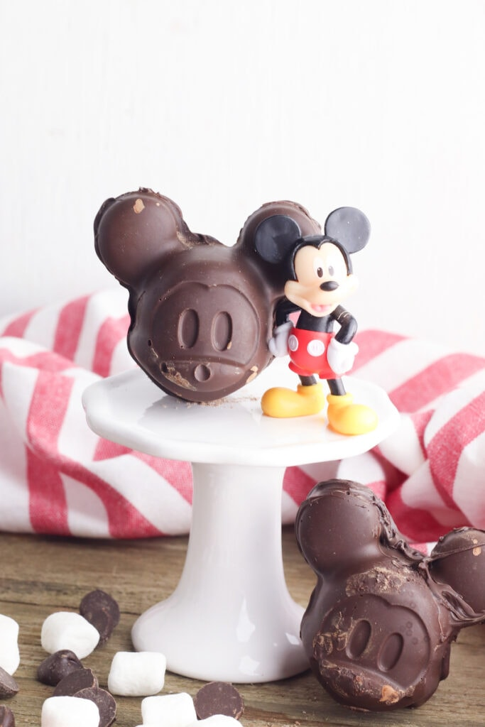 Mickey Mouse shaped chocolate molds on white pedestal with marshmallows around