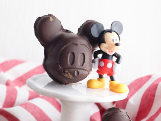 mickey shaped chocolate mold on white pedestal next to plastic Mickey Mouse figurine