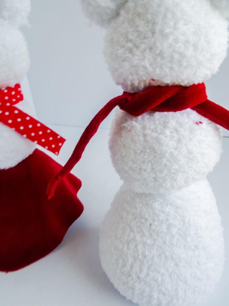 white sock snowman with red scarf tied around neck