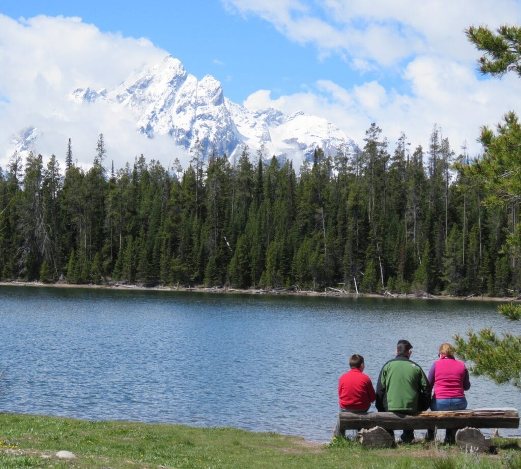 family sitting on a bench looking at Gran Teton Mountains across from lake