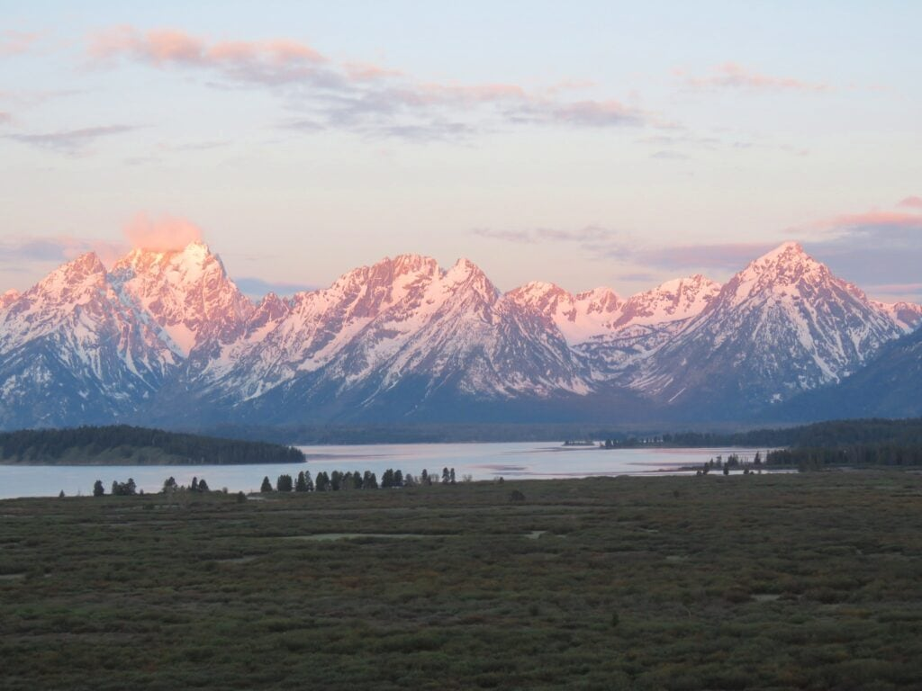 pink light of sunrise bathing Grand Teton mountain range