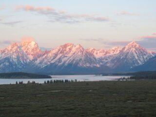 pink light of sunrise bathing Grand Teton mountain range
