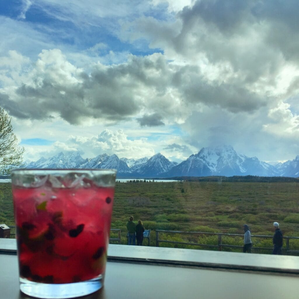 huckleberry cocktail on table with Mountain View in distance