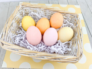 Easter Eggs dyed With Kool Aid in basket on yellow background